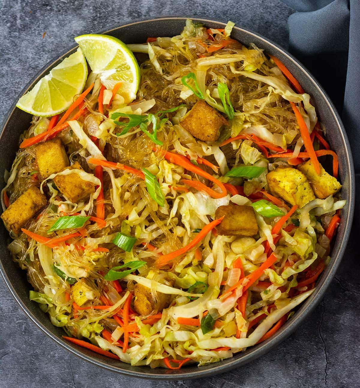 Close up overlay of pancit bihon - noodle stir fry in a dark grey bowl with lemon wedges and spring onion for garnish on a grey background and grey napkin
