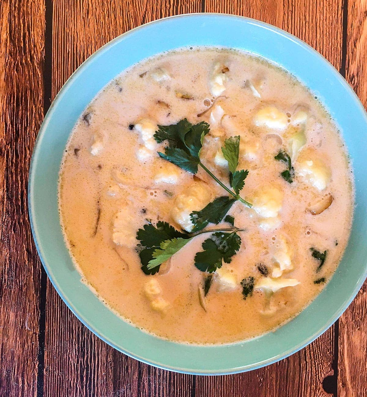 Overlay coconut stew in a blue bowl on a brown background