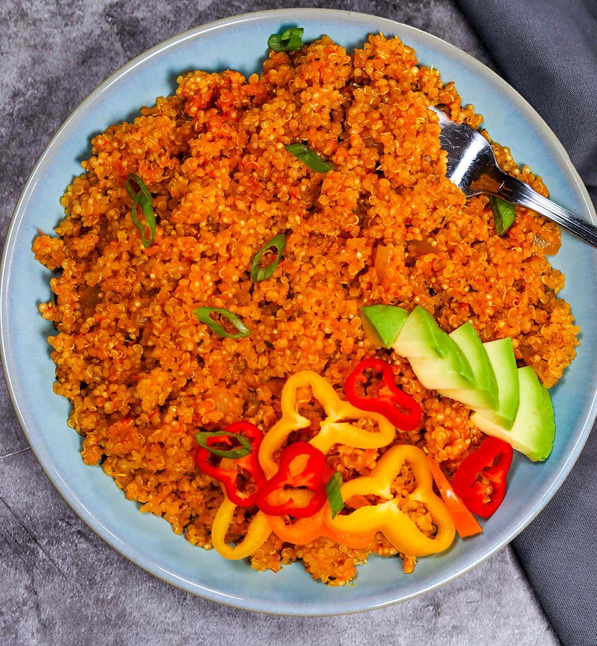 close up image of Jollof Quinoa in a blue bowl on a grey background
