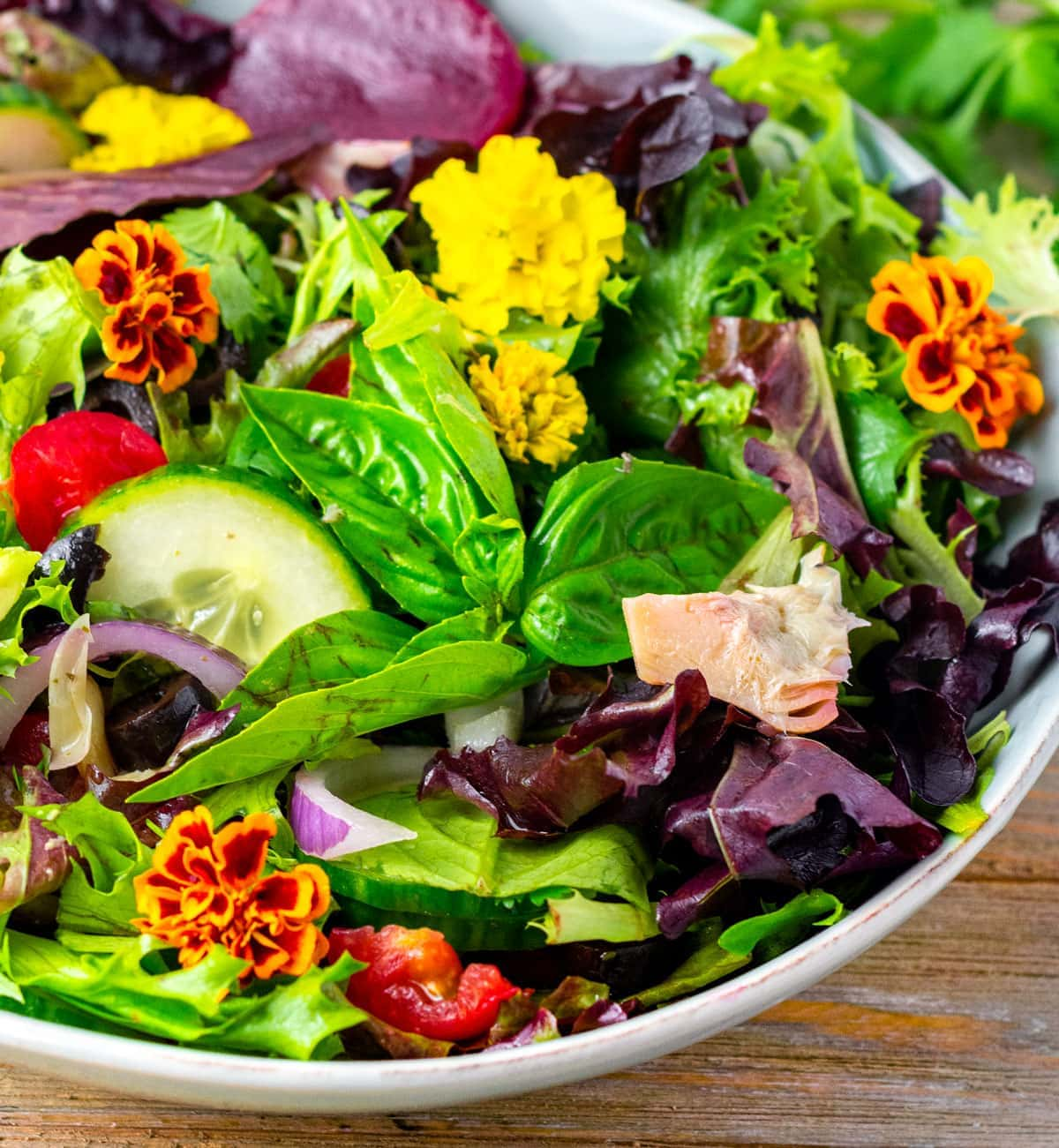 close up of spring salad mix in a blue bowl, basil, edible flowers on a wooden board