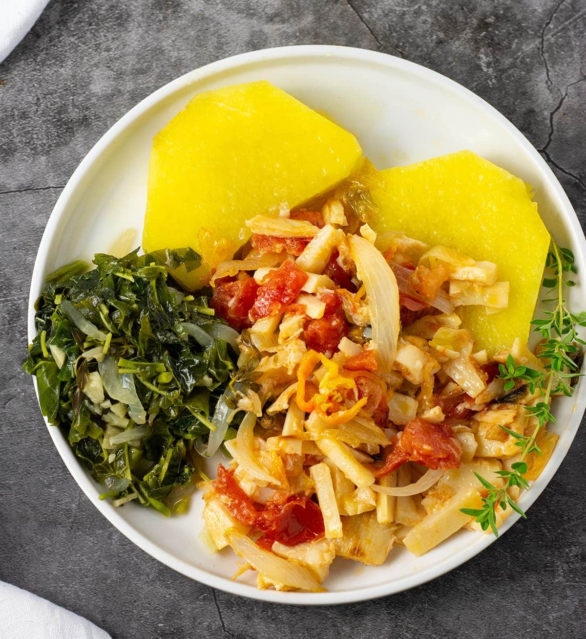 vegan salt fish recipe on a white plate with yellow yam, and callaloo on a grey background