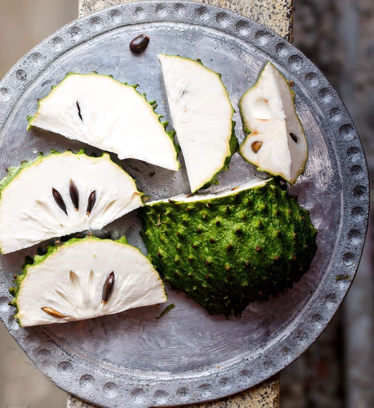 Soursop cut into slices showing white flesh on a silver platter