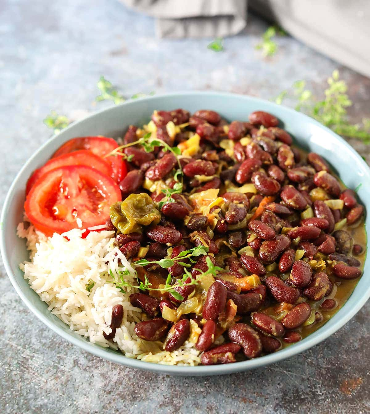 Straight on kidney bean curry Jamaican style with white rice tomato slices in a blue bowl with a fork on a blue and brown concrete background garnished with thyme