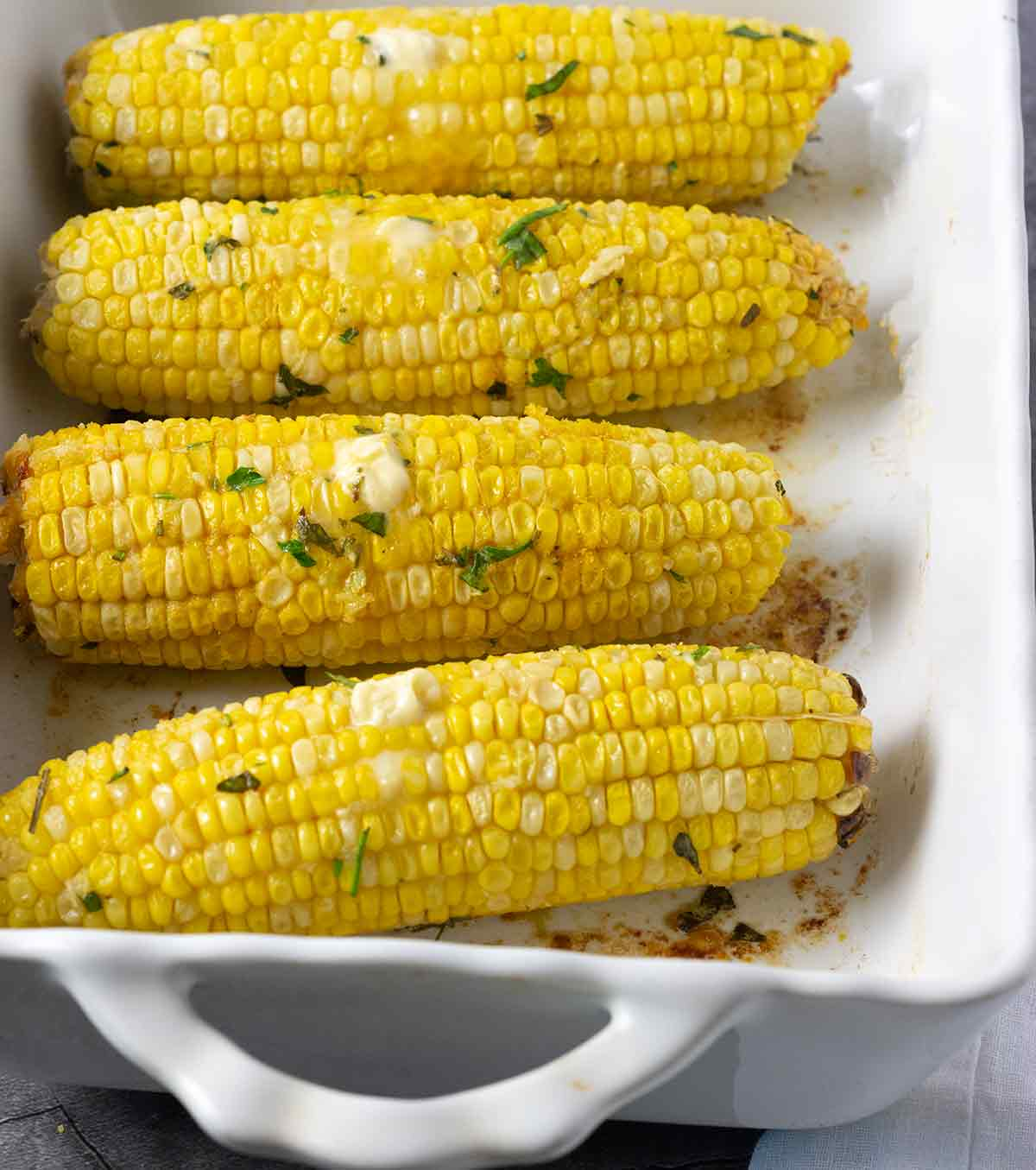 Close up baked corn in a white baking dish