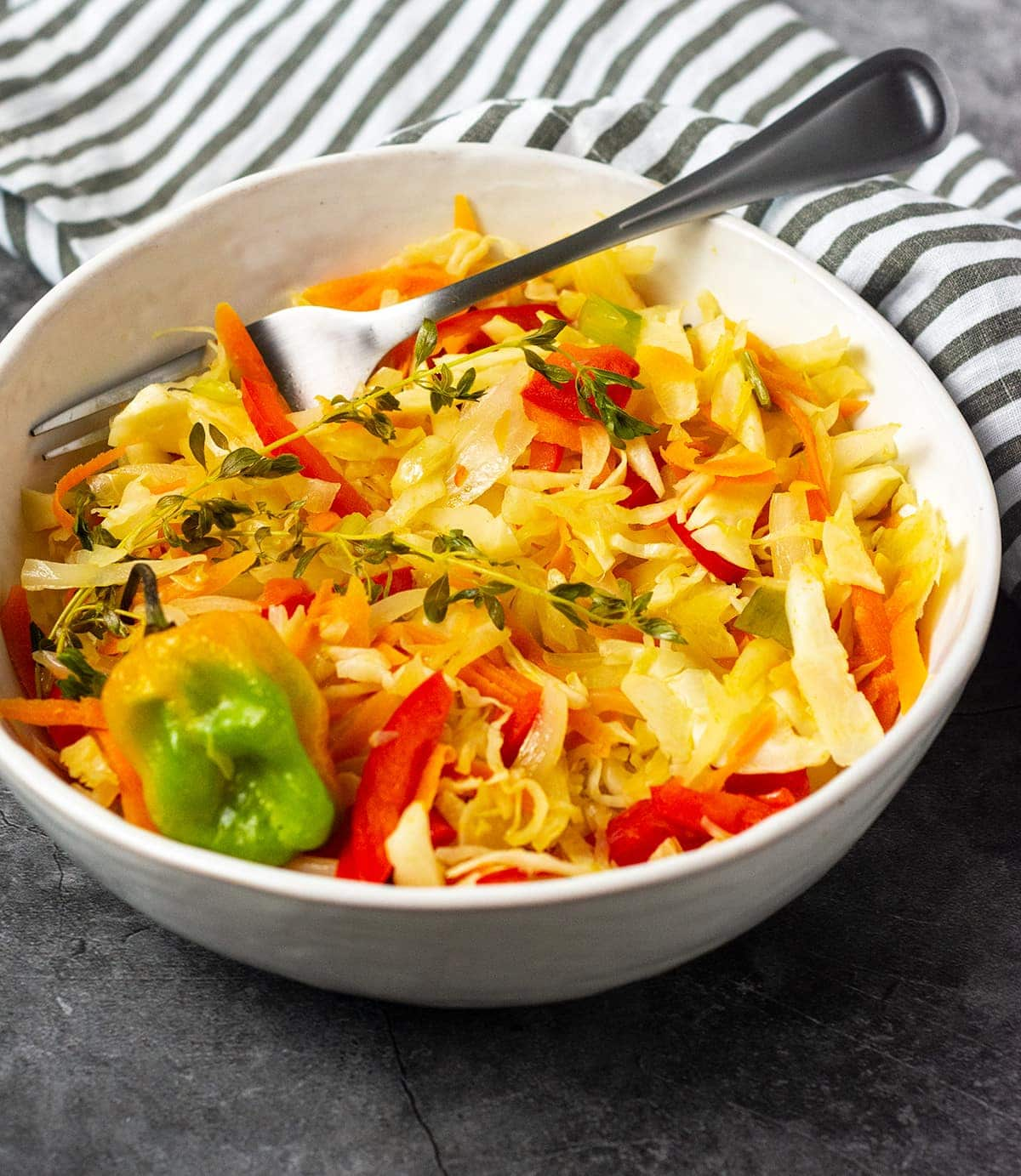 Jamaican steamed cabbage straight on recipe on a grey background with white bowl