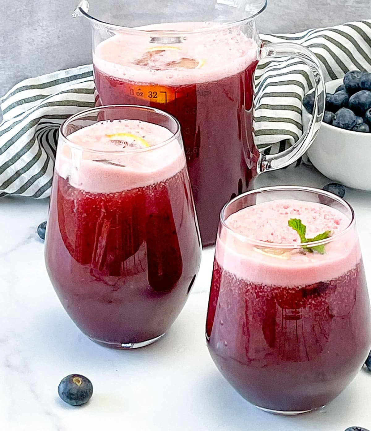 Blueberry lemonade in a pitcher and glasses on white background