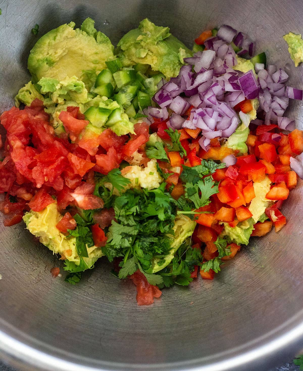Chopped ingredients for loaded guacamole in a silver bowl