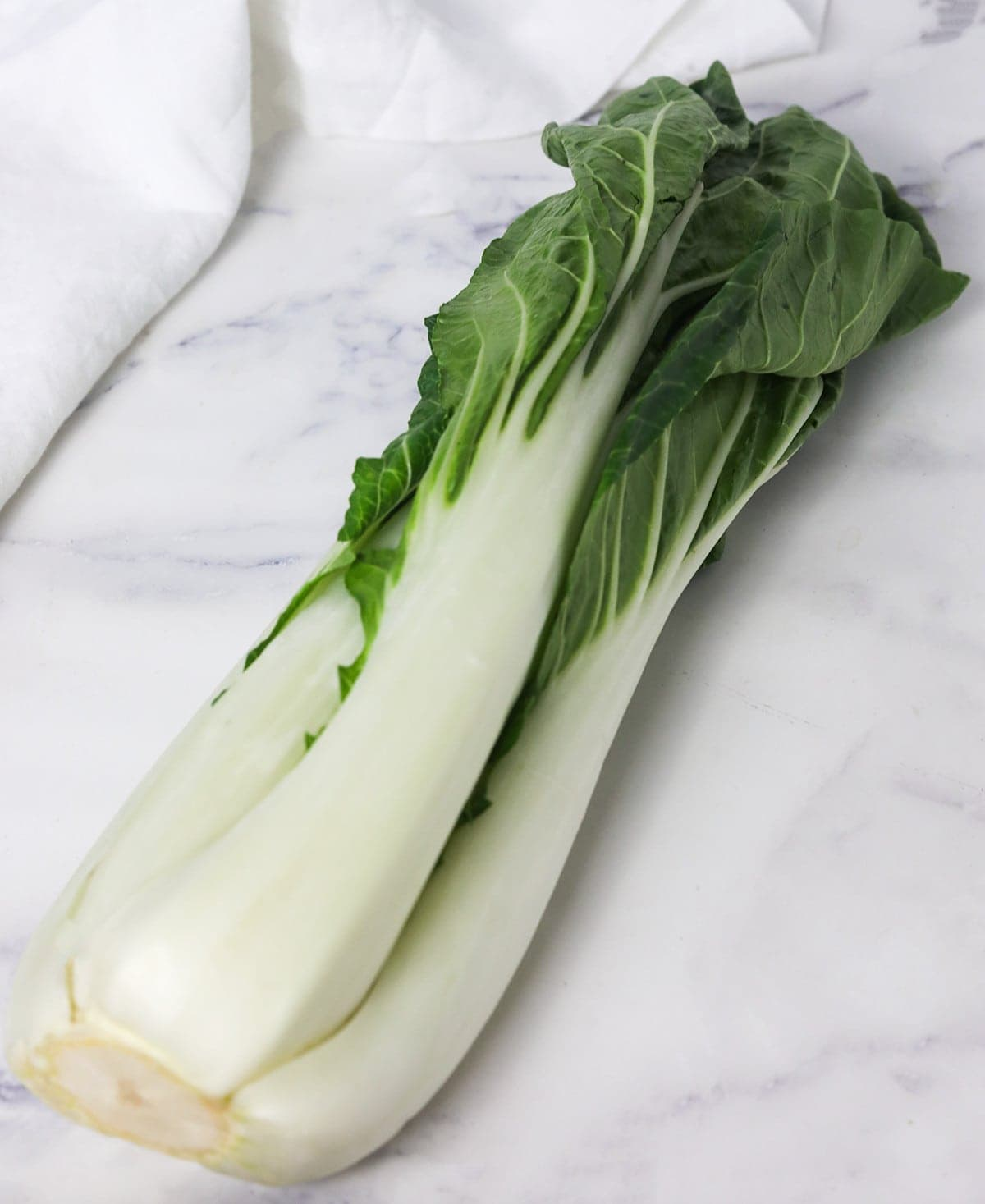bok choy on a white marble with a white napkin