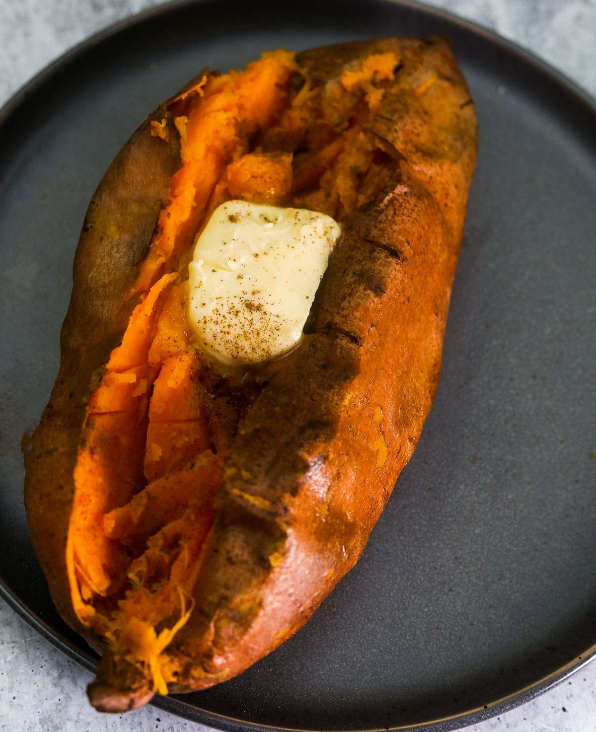 close up of baked sweet potato in air fryer on a grey plate