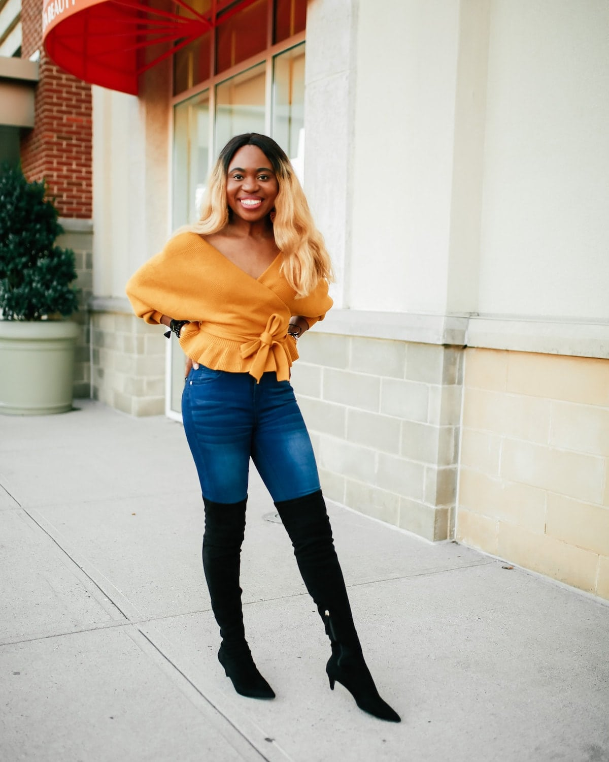 Crushing on this super chic peplum hem sweater outfit paired with high-waist jeans and black suede over the knee boots. No better way to make a statement this season than with a chic, cozy, and comfy open back wrap sweater that's under $30 and available on Amazon Prime. #otkboots #bootsforwomen