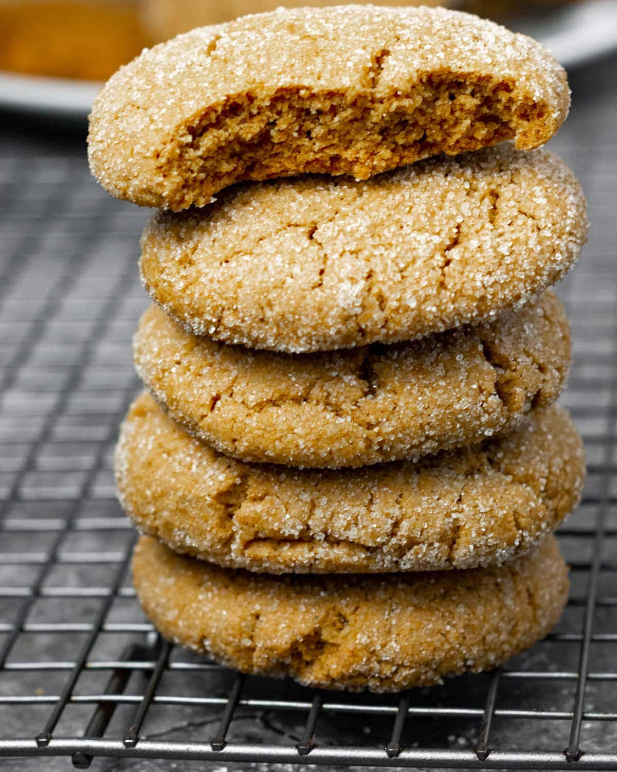 Vegan molasses cookies stacked vertically on a white plate with a plate of cookies in the background. on a burlap napkin on a cooling raf