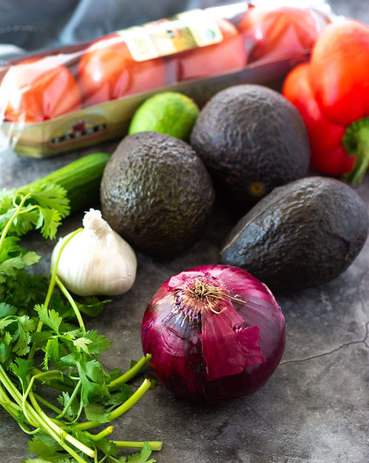 Loaded guacamole ingredients on a grey background