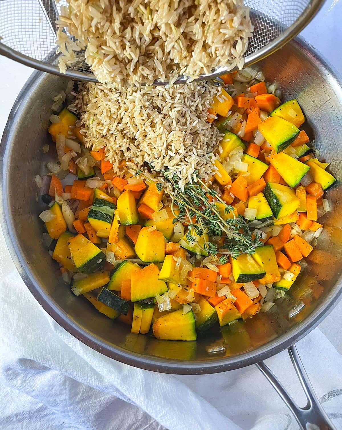 pouring rice with pumpkin and vegetables in a saucepan