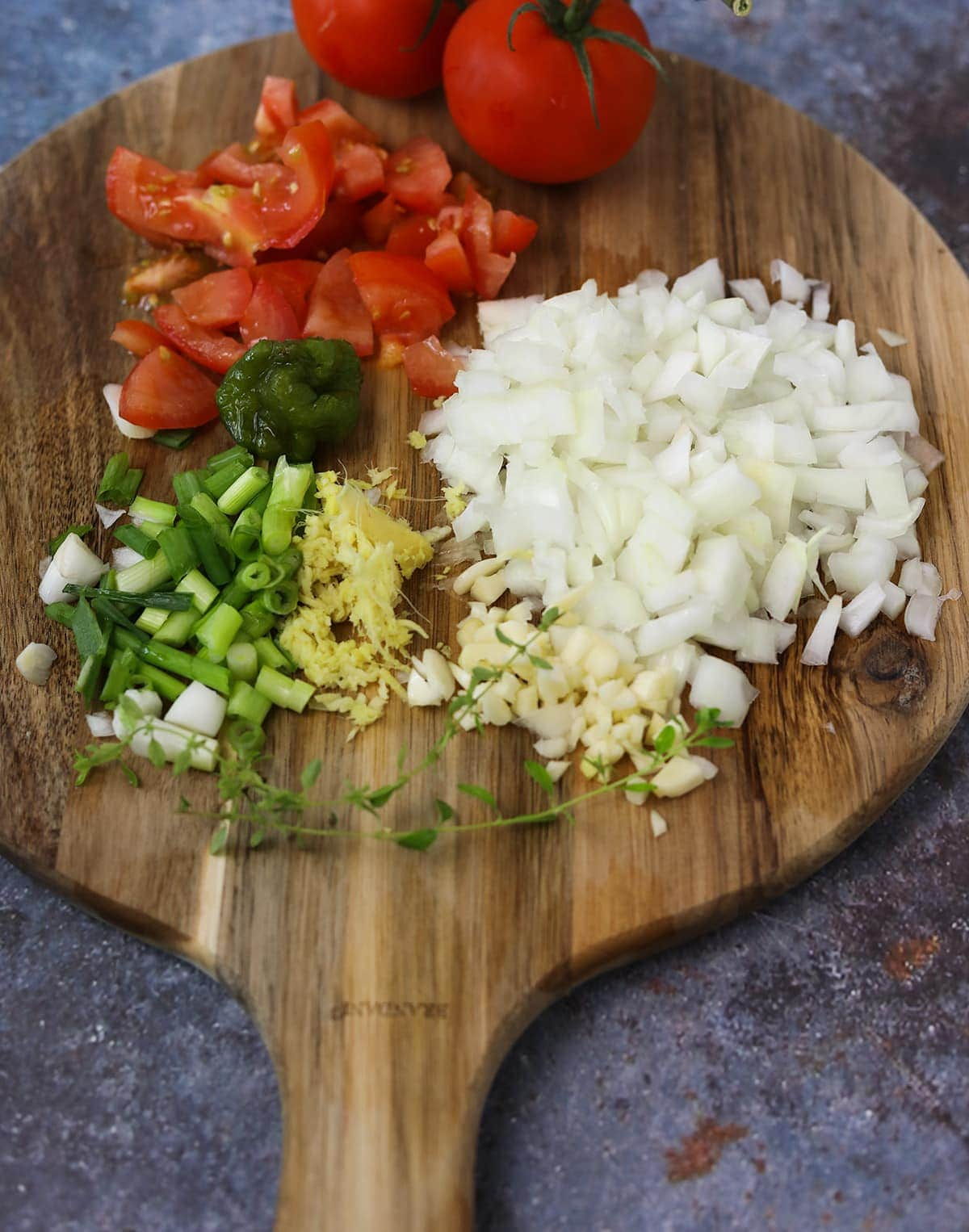 Ingredients for kidney bean curry on a wooden board on blue background