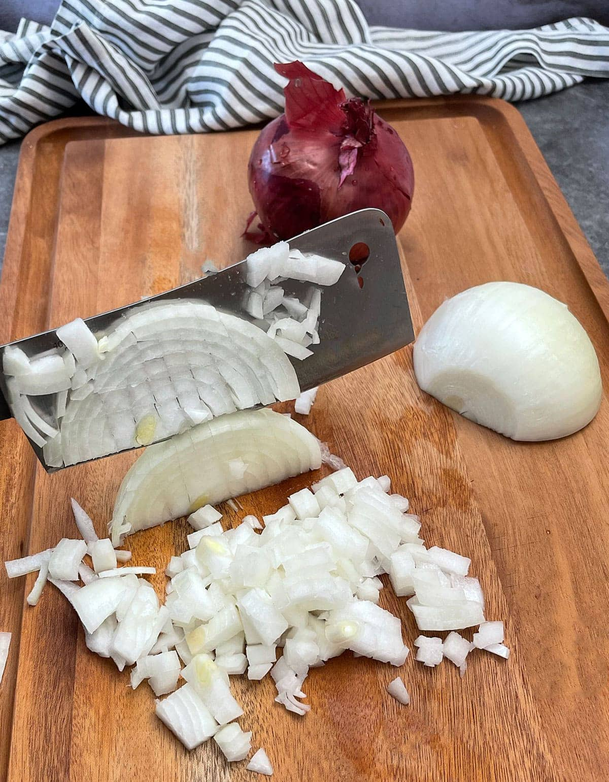 Dicing onion with a knife on the cutting board