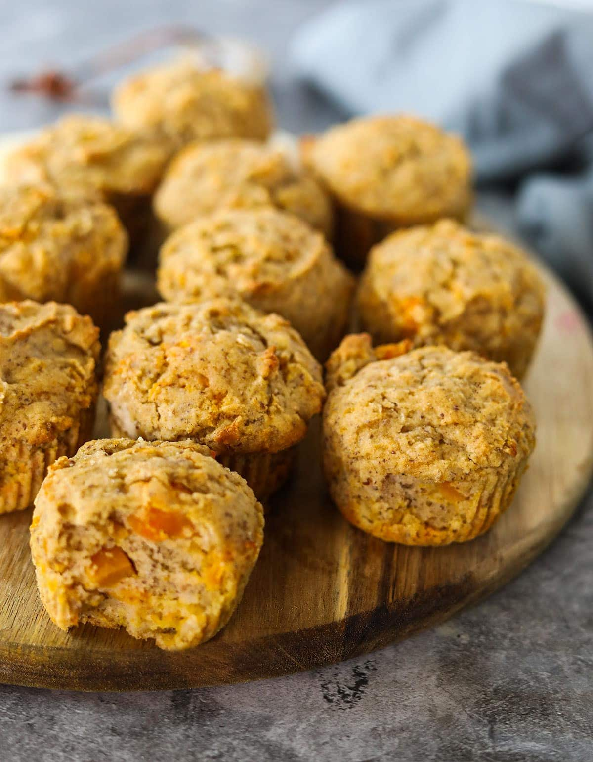 Gluten-free vegan butternut quash muffins on a round cutting board on a grey concrete with a grey apron