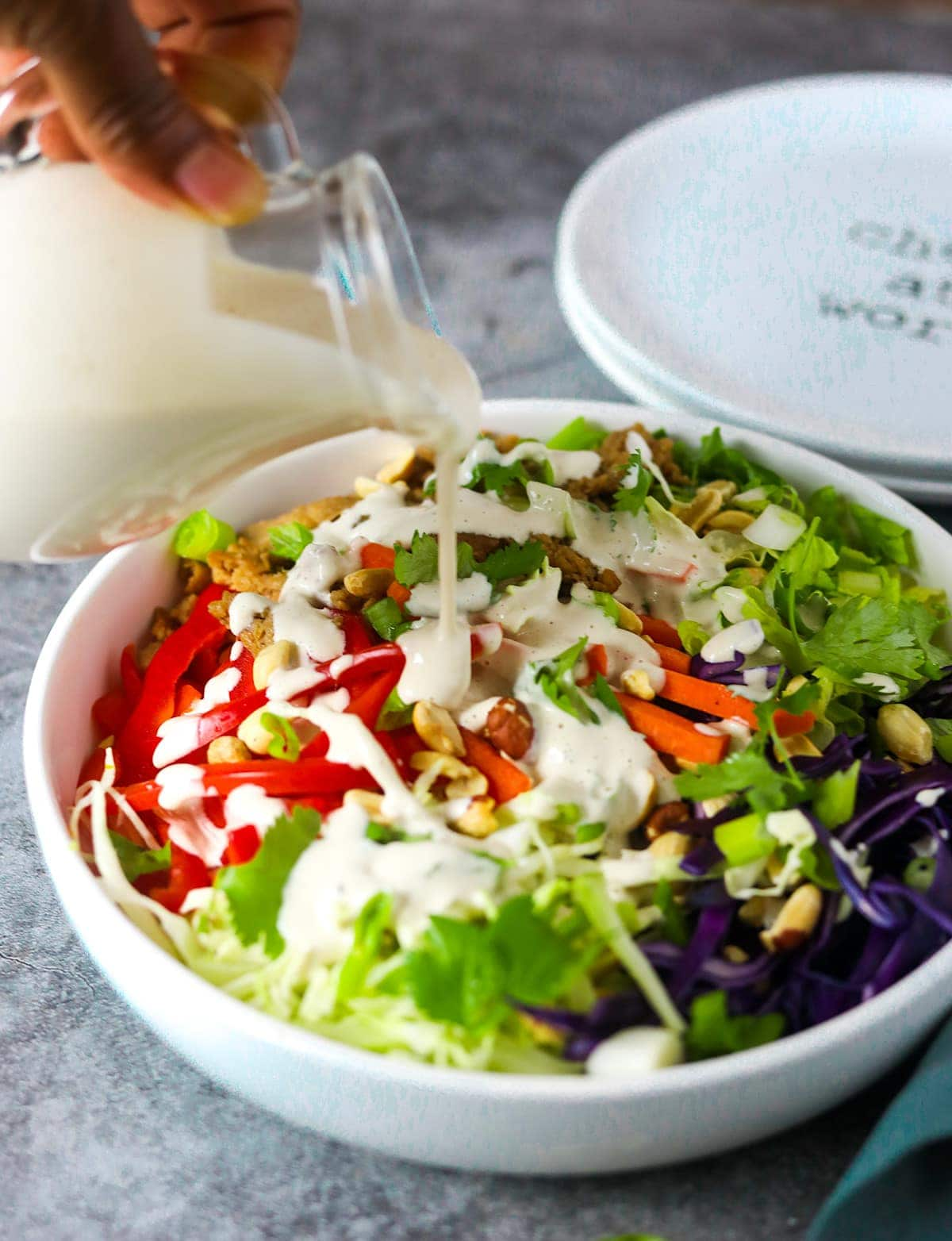 pouring salad dressing from a glass container on asian salad in a white bowl