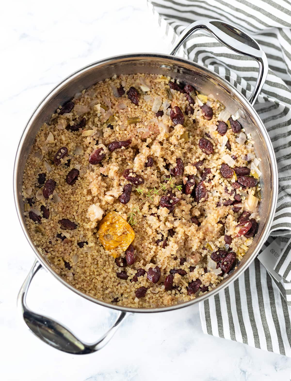 Jamaican quinoa and peas quinoa cooked with dark red kidney beans on.a white background with a black and white striped napkin