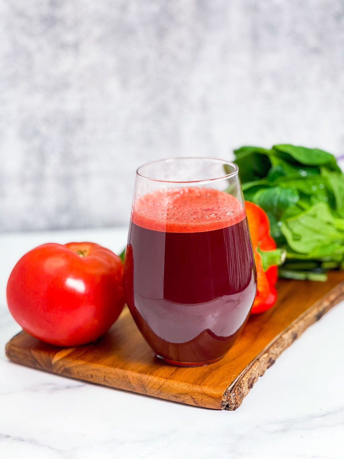 V8 juice on cutting board with tomato, bell pepper and spinach on a white board