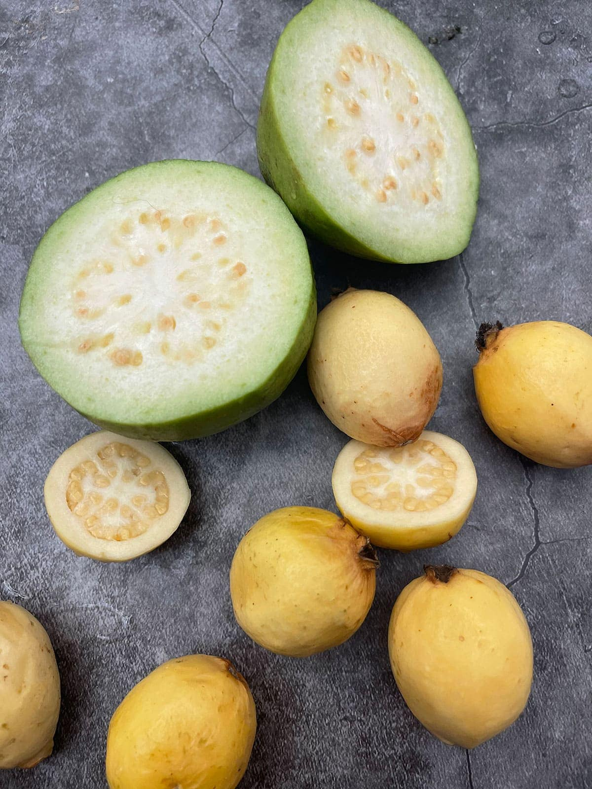 White guava and yellow guava on a grey background