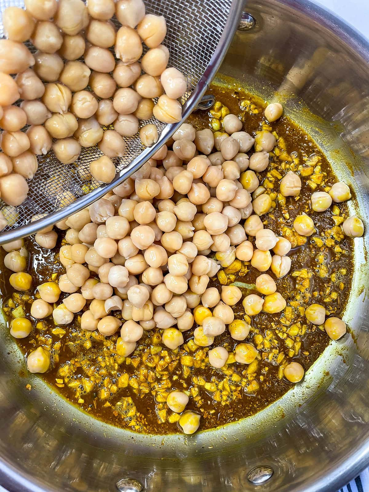 curry chana with chickpeas being added to saucepan