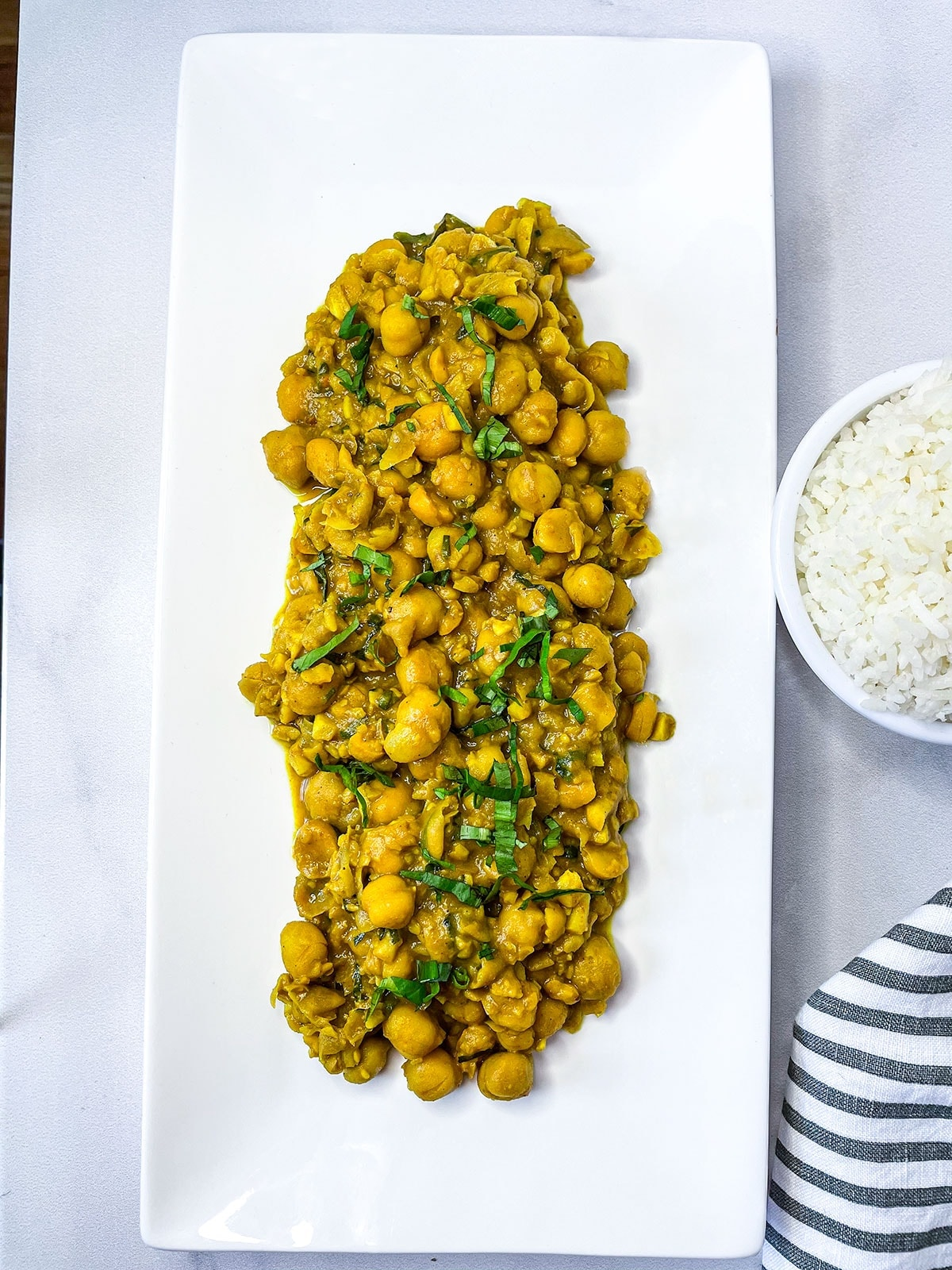 overlay curry channa on a white rectangular plate with a black and white stripe