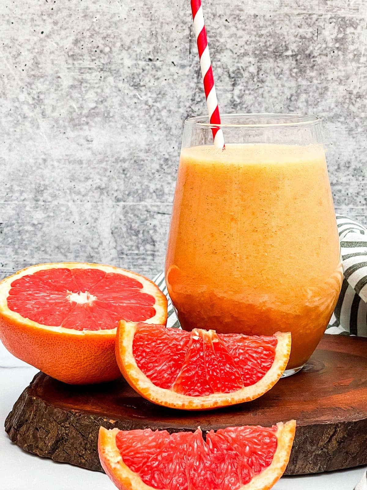Grapefruit smoothie in a glass with a striped orange and white straw, cut pieces of grapefruits on a wooden background