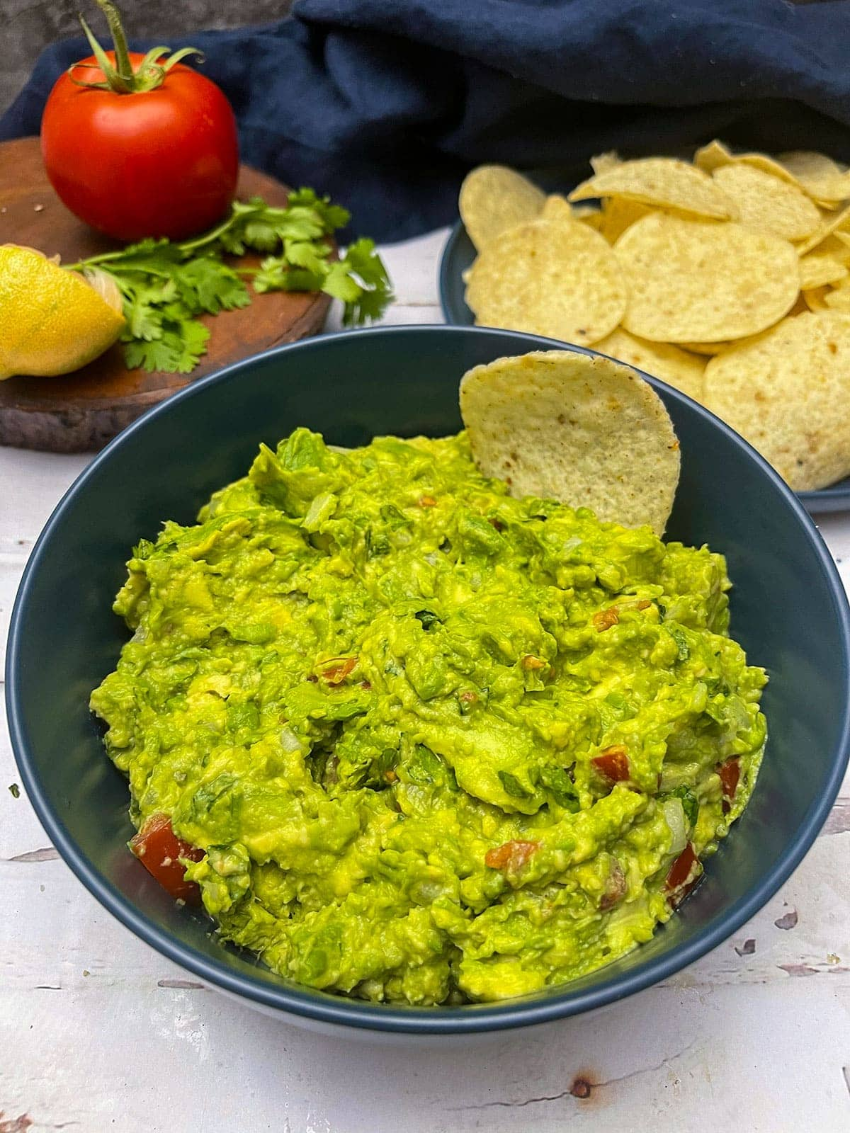 close up guacamole in a blue bowl on white background