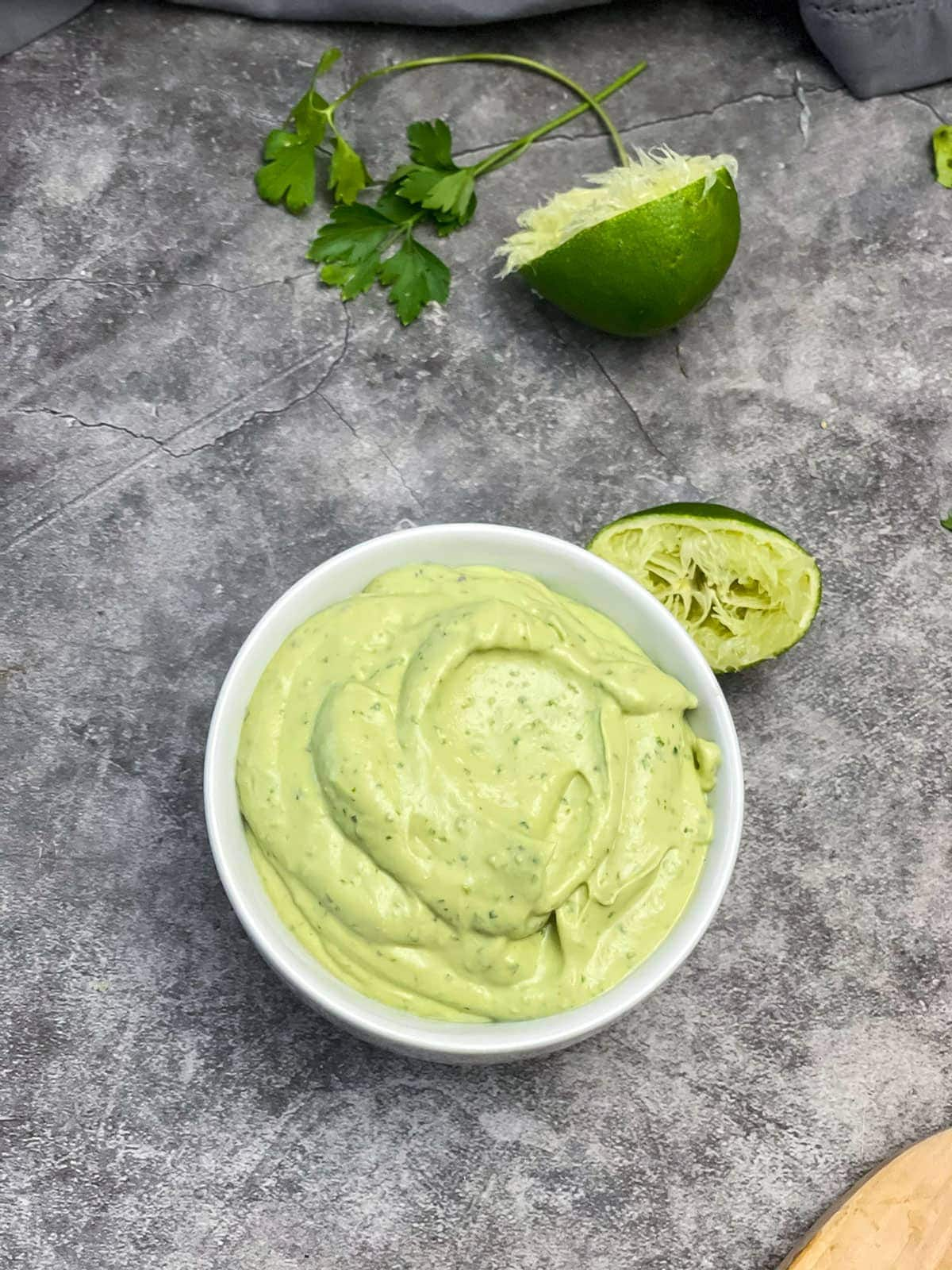 overlay avocado lime sauce in a white bowl on a grey background