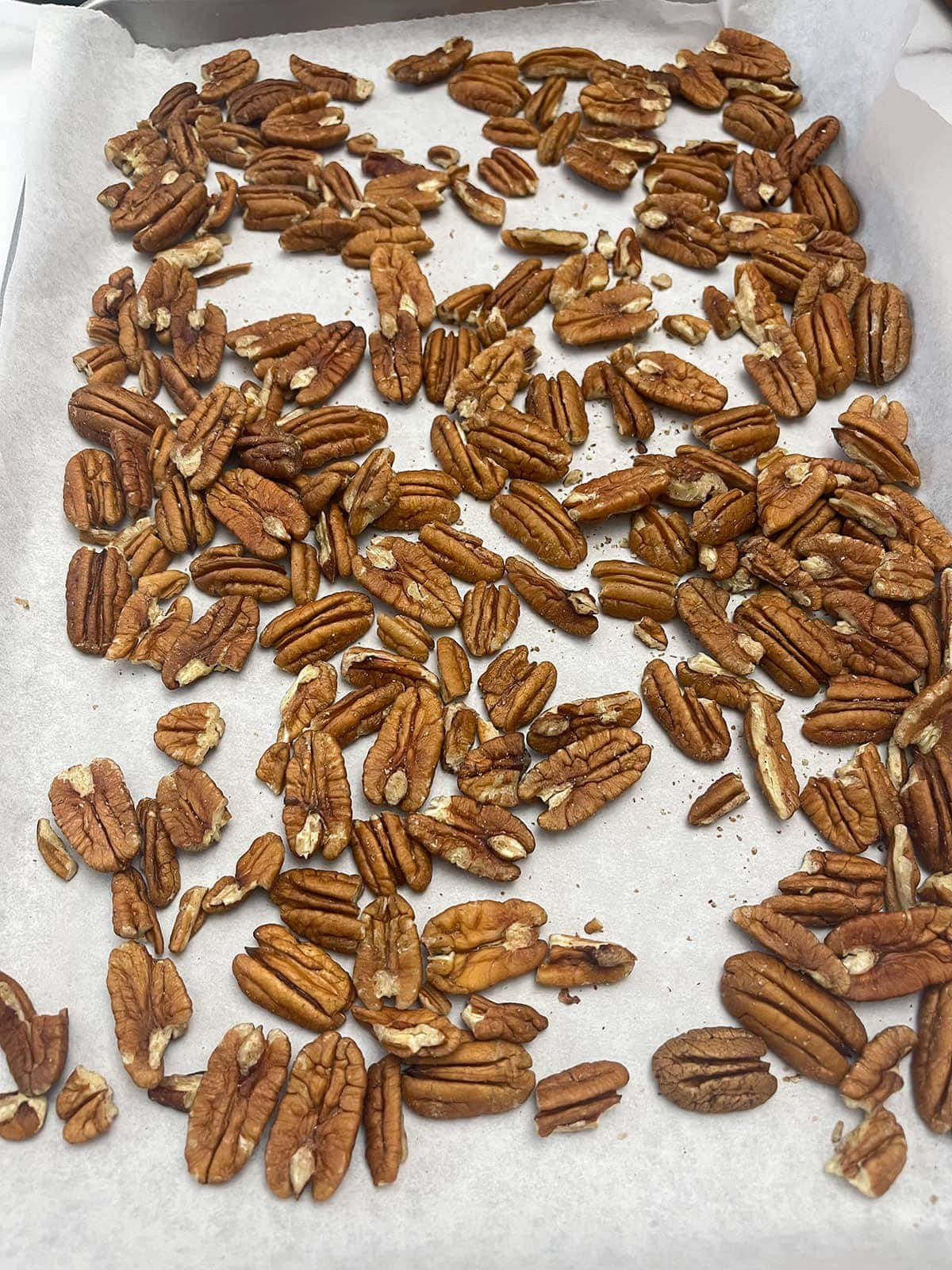 pecans on a baking sheet about to get toasted