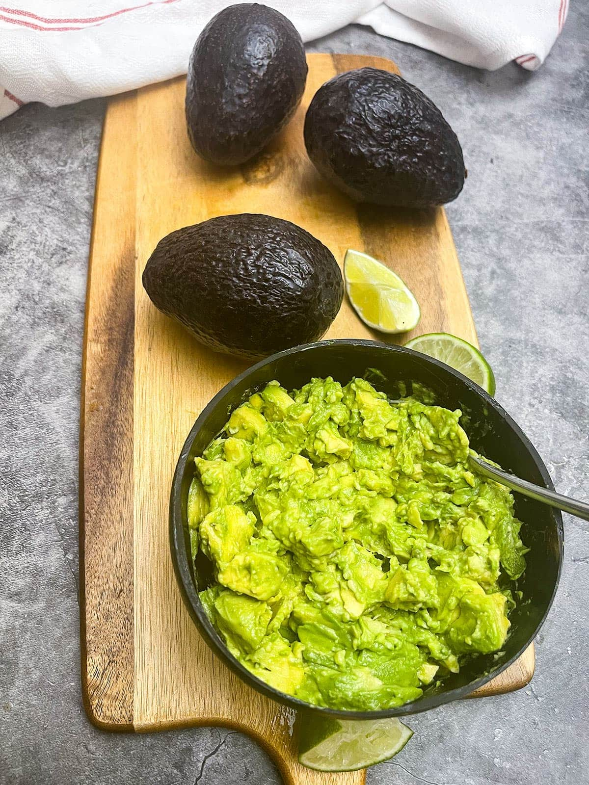 mashed avocado in a wooden bowl on a wooden boafdo