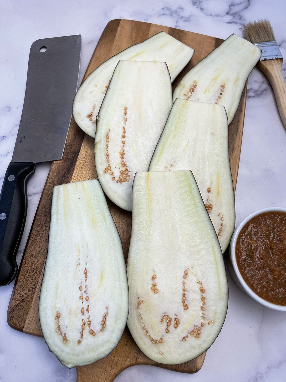 eggplant slices on a cutting board on a white background with a cleaver knife on the side
