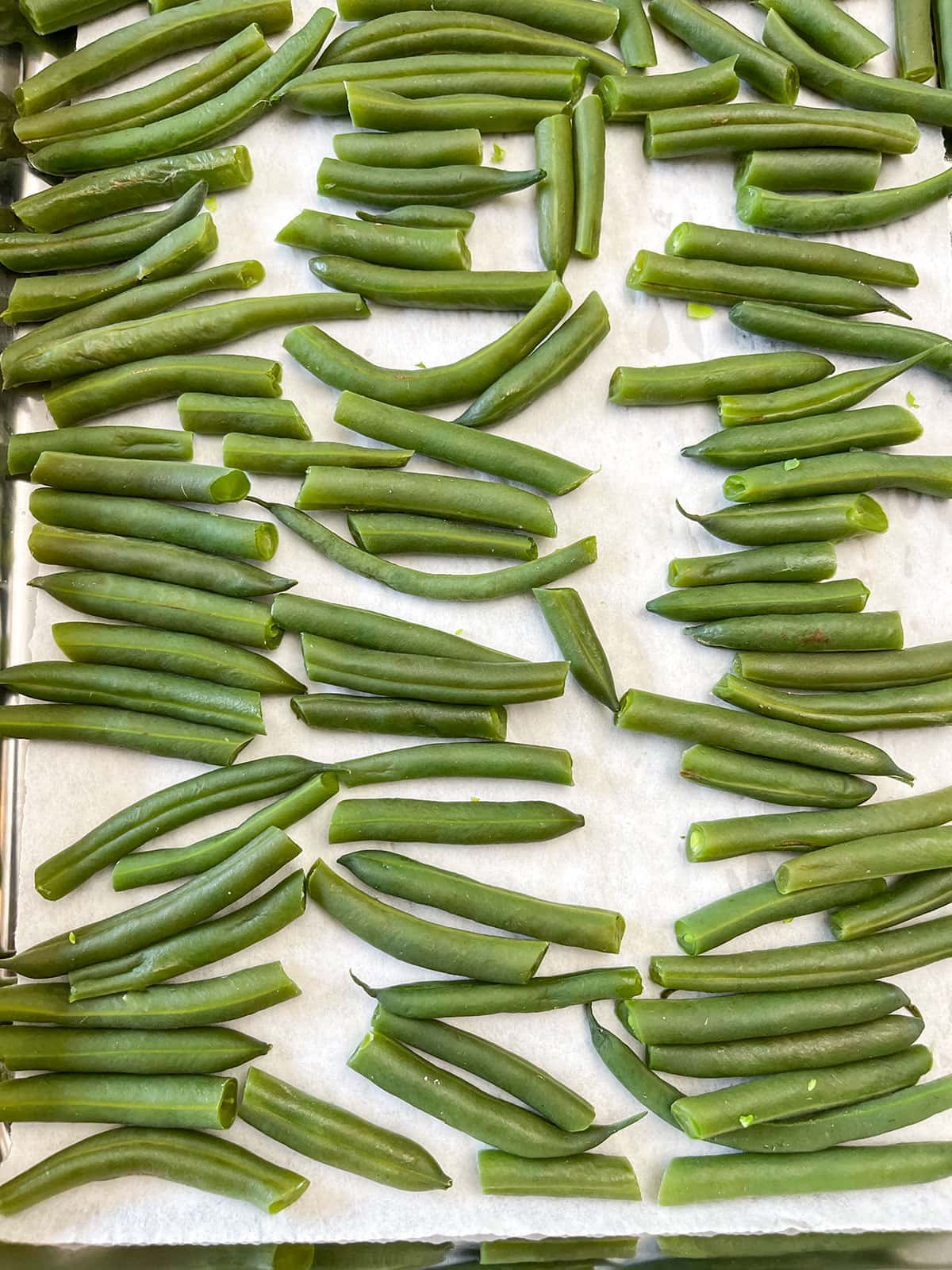 blanched green beans on a baking sheet in a single layer