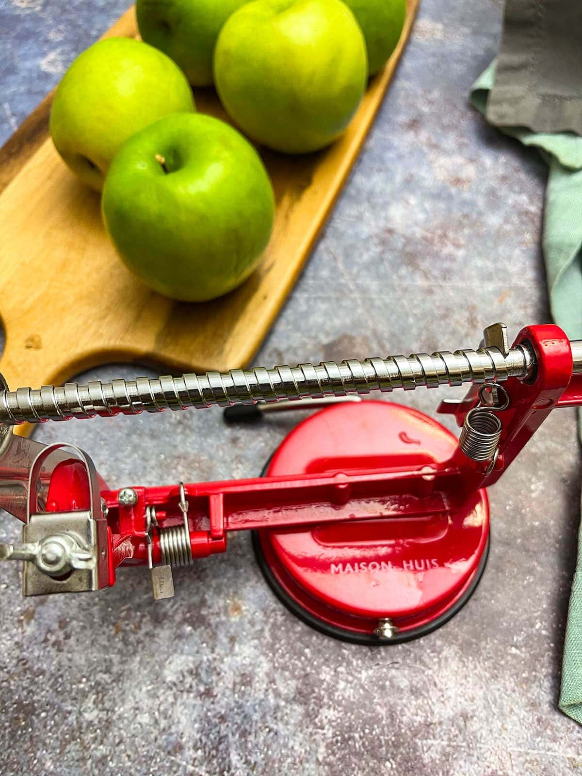 whole apples on cutting board with apple peeler