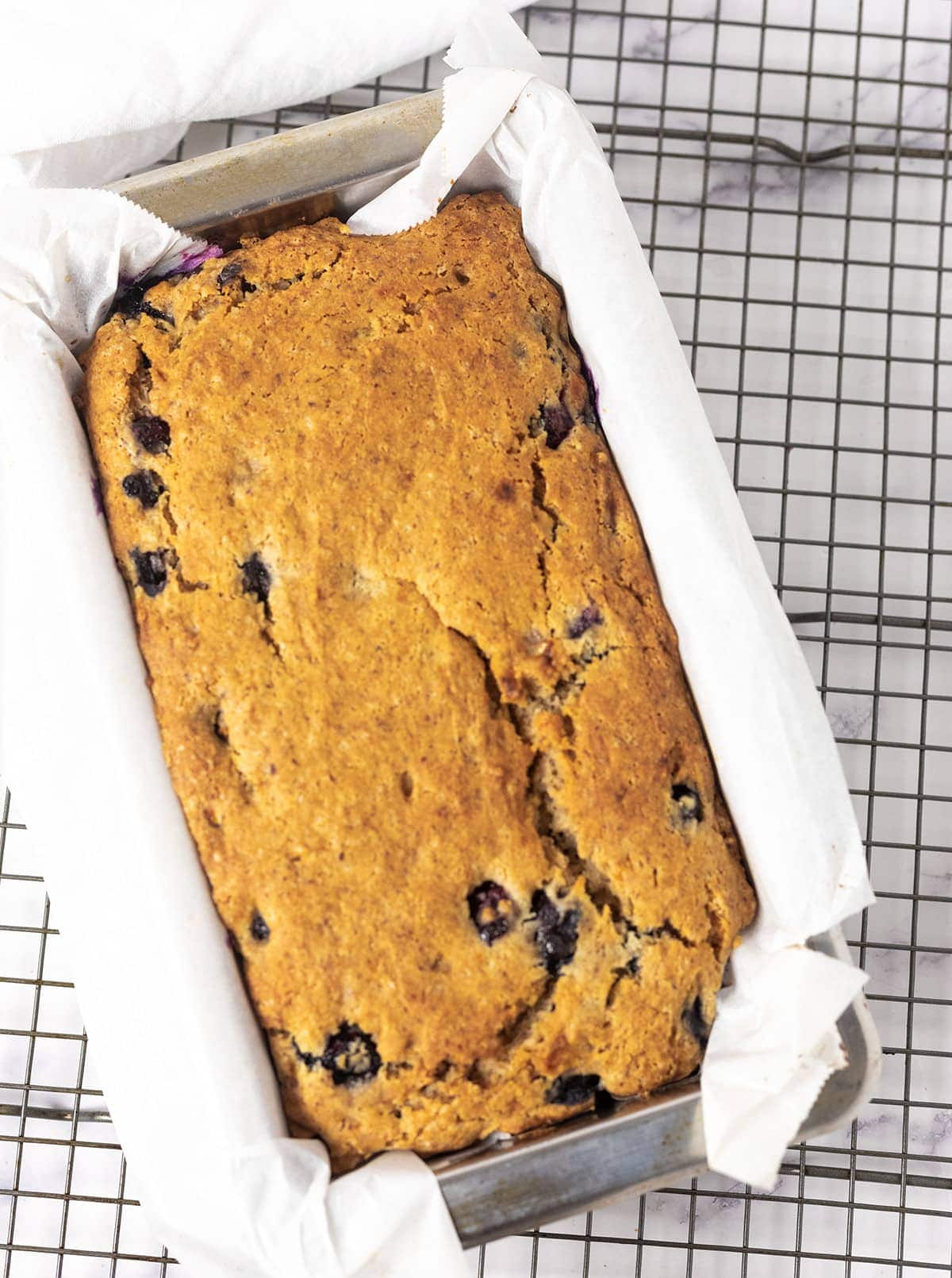 overlay of gluten-free vegan banana bread in a pan lined with parchment paper on a wire rack