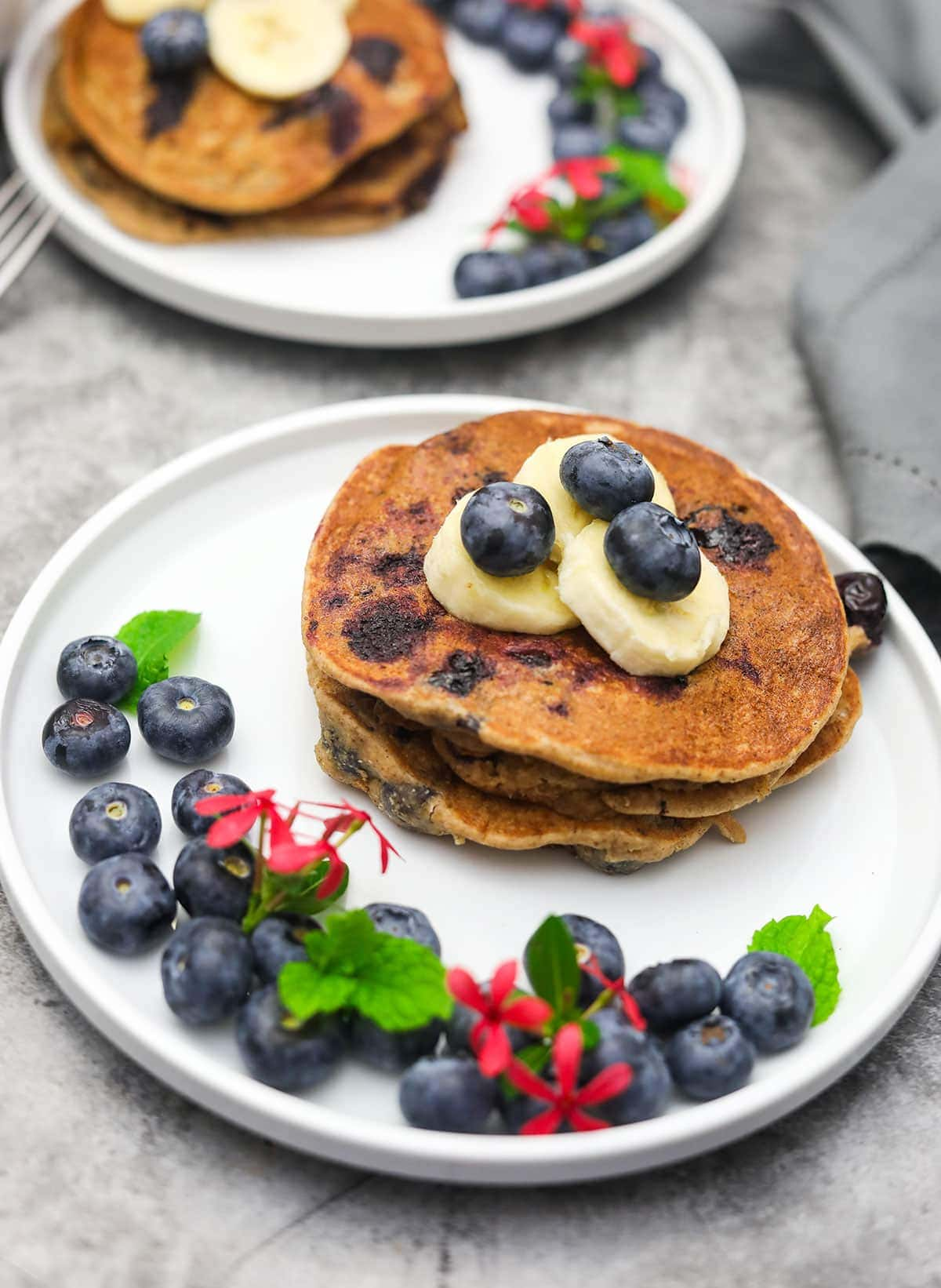 blueberry banana oatmeal pancakes stacked on two white plates decorated with blueberries, banana slices and pink flower on a concrete background
