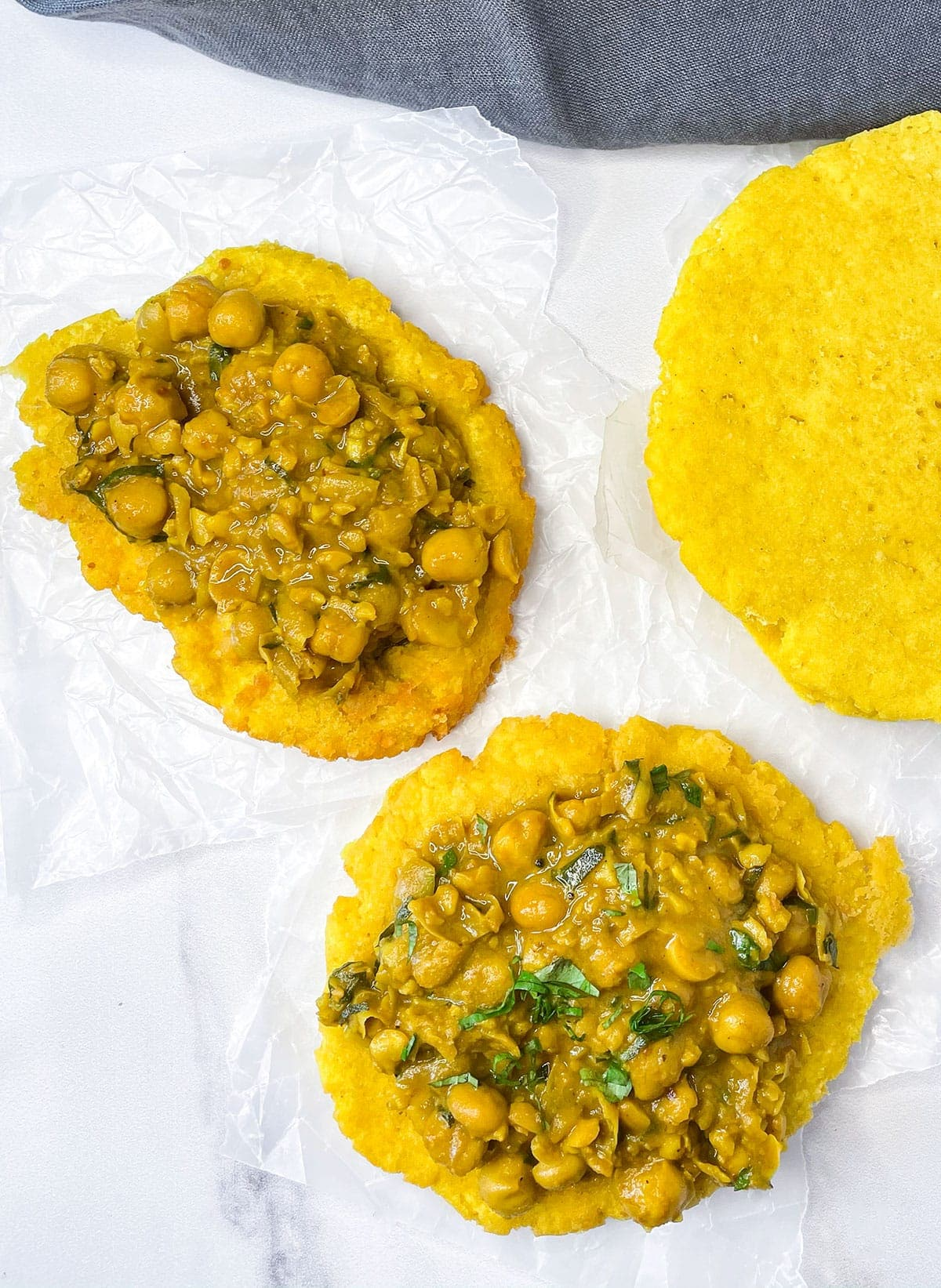 overlay of doubles flatbread topped with curry chana on a white background