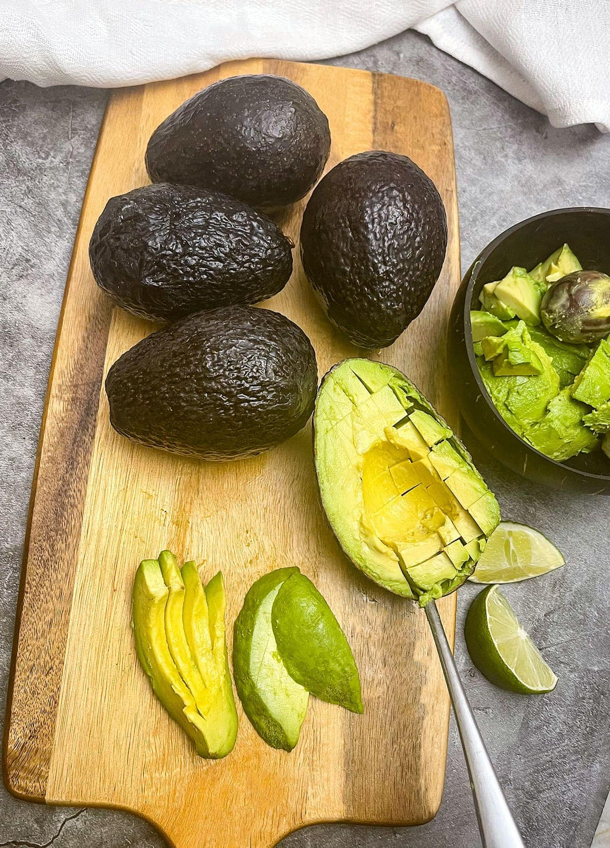 scooping avocado vs slicing on a wooden background