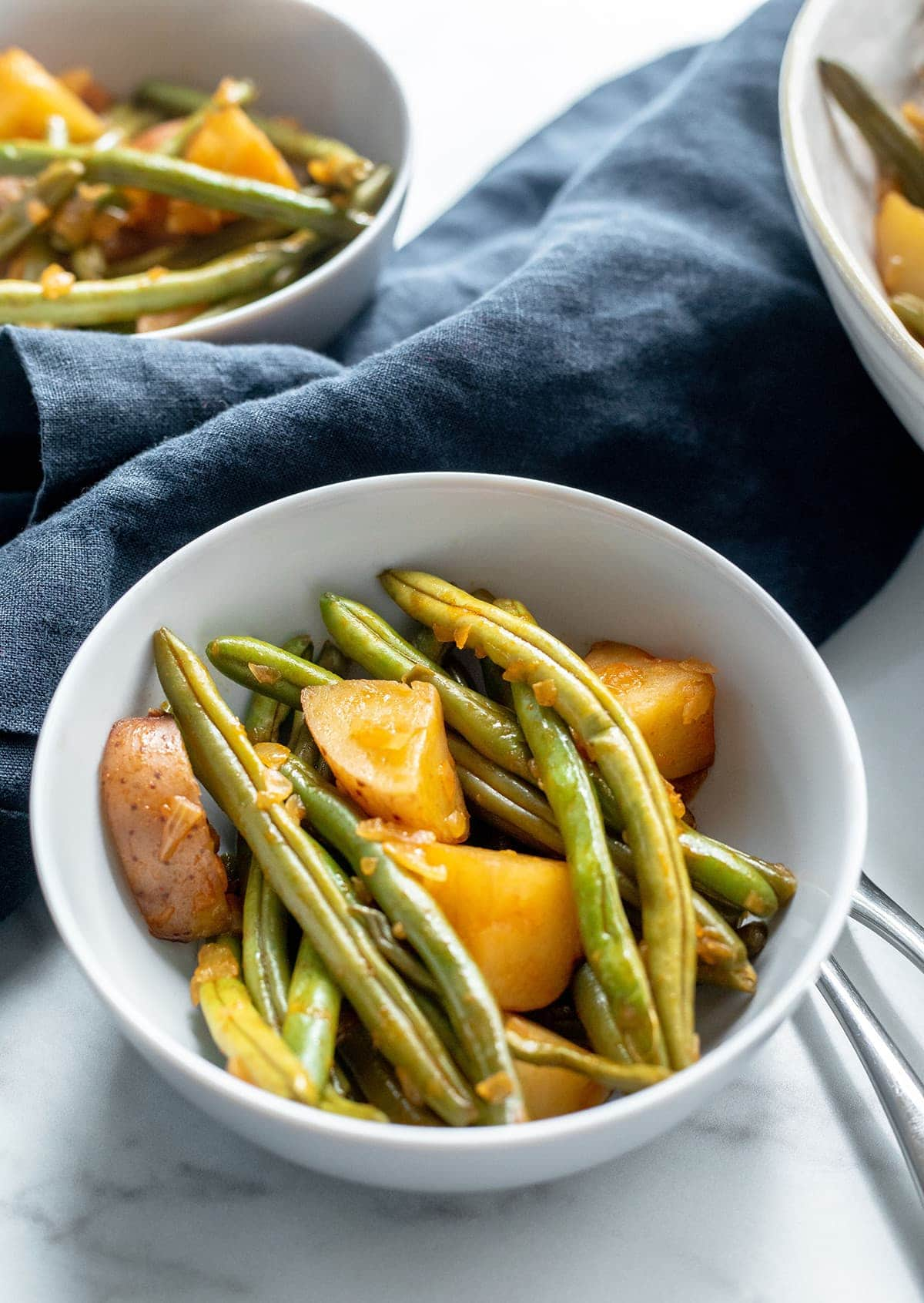 Southern Green Beans and potatoes in 3 white serving bowls on a white background with a blue napkin