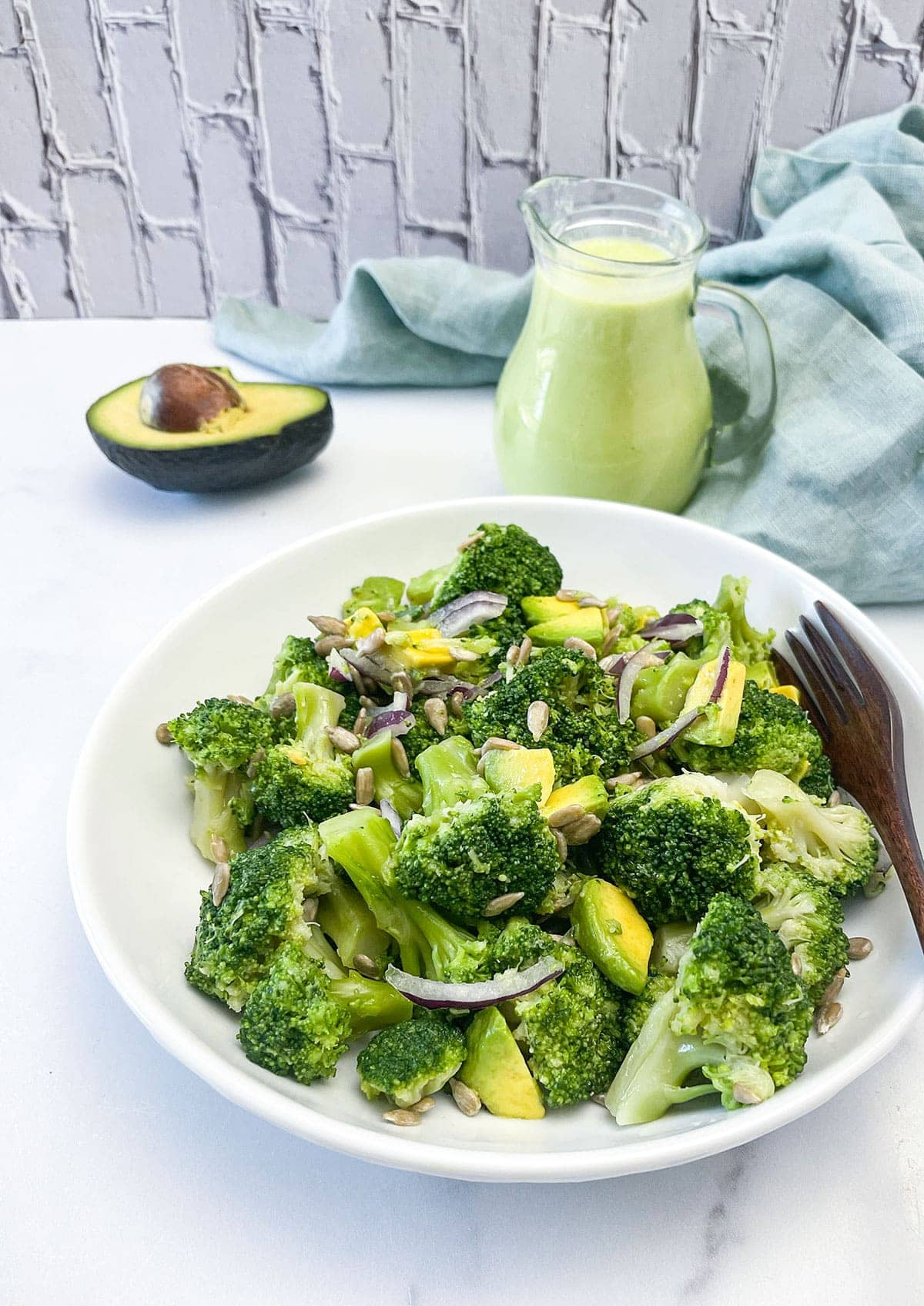 broccoli salad on a white plate with a salad dressing in the background and avocado