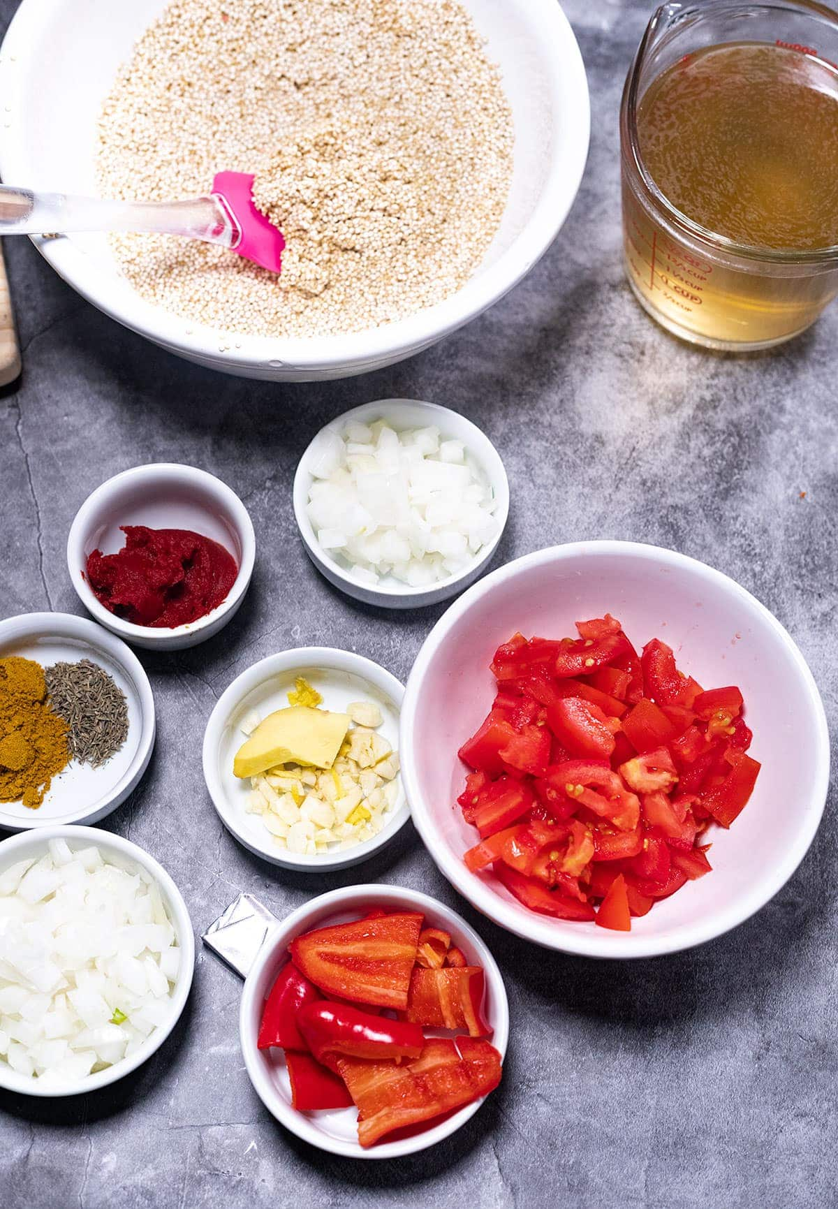 ingredients for jollof quinoa on a grey background