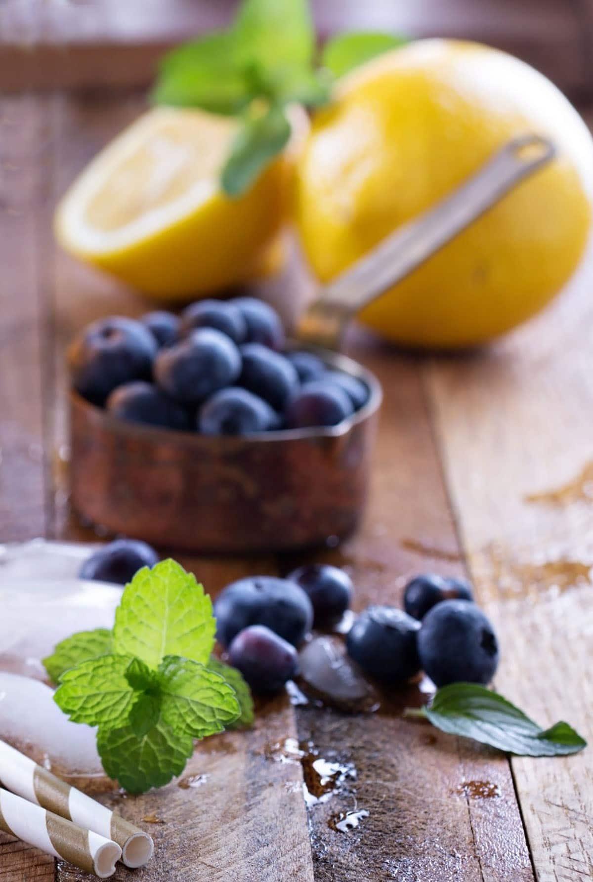 blueberry lemonade ingredients, blueberries, lemon on a wooden background