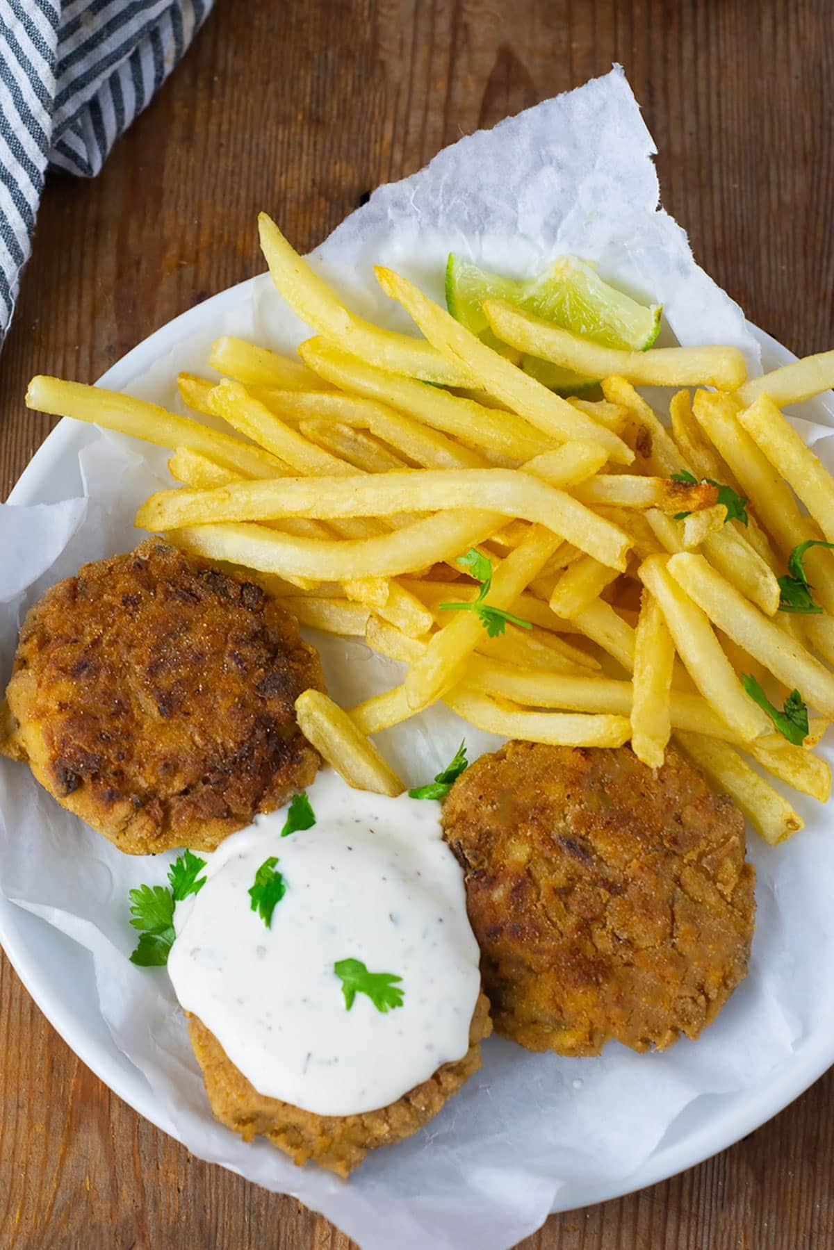 Overlay vegan crab cakes on a white plate with fries