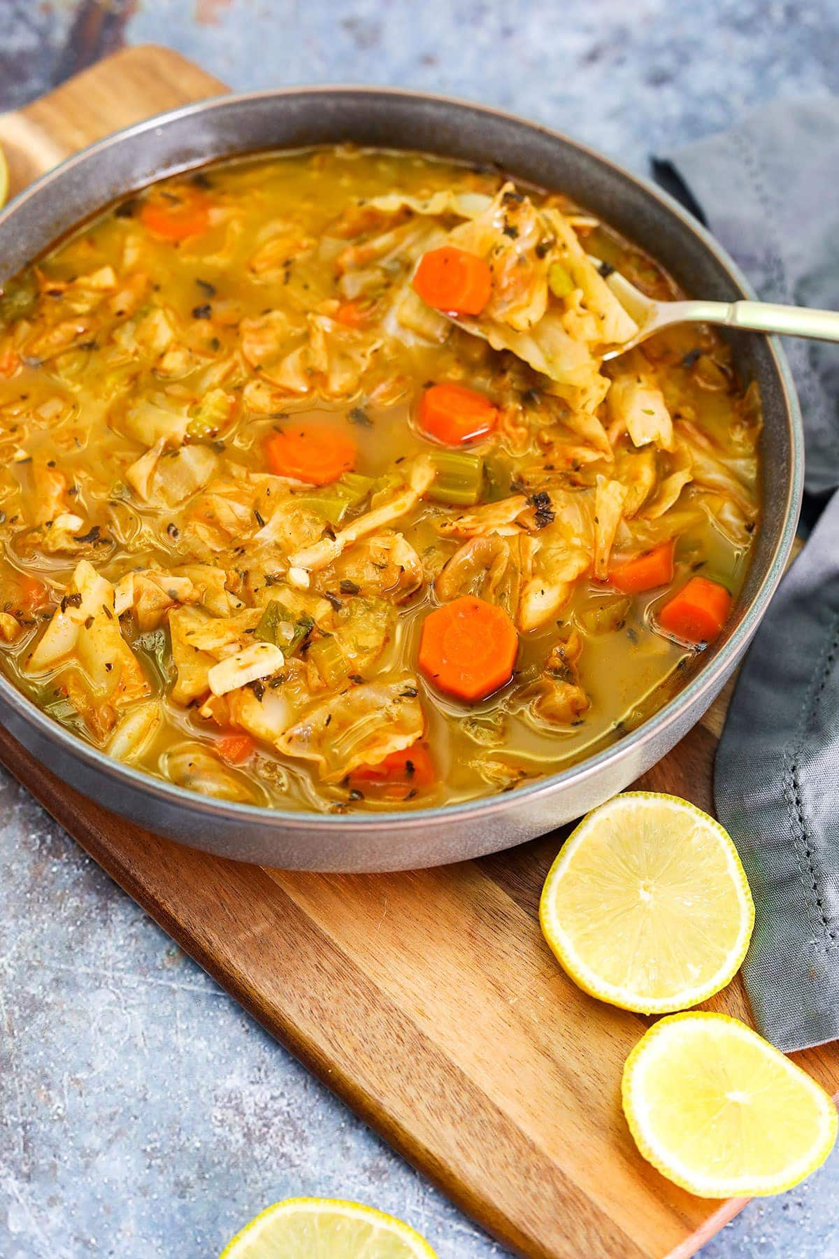 Gluten-free vegan cabbage soup, in white soup bowls with carrots and vegetable broth on a grey background
