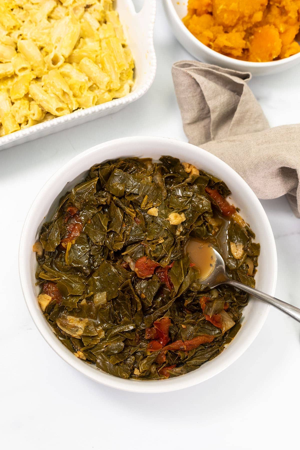 overlay of collard greens in a white bowl on a white background with mac and cheese in the background and candied yams