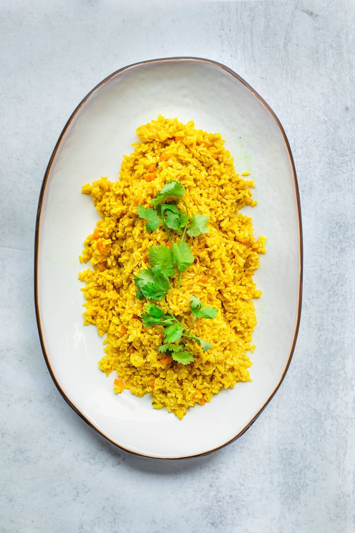 Overlay of yellow turmeric coconut rice garnished with cilantro on a white plate