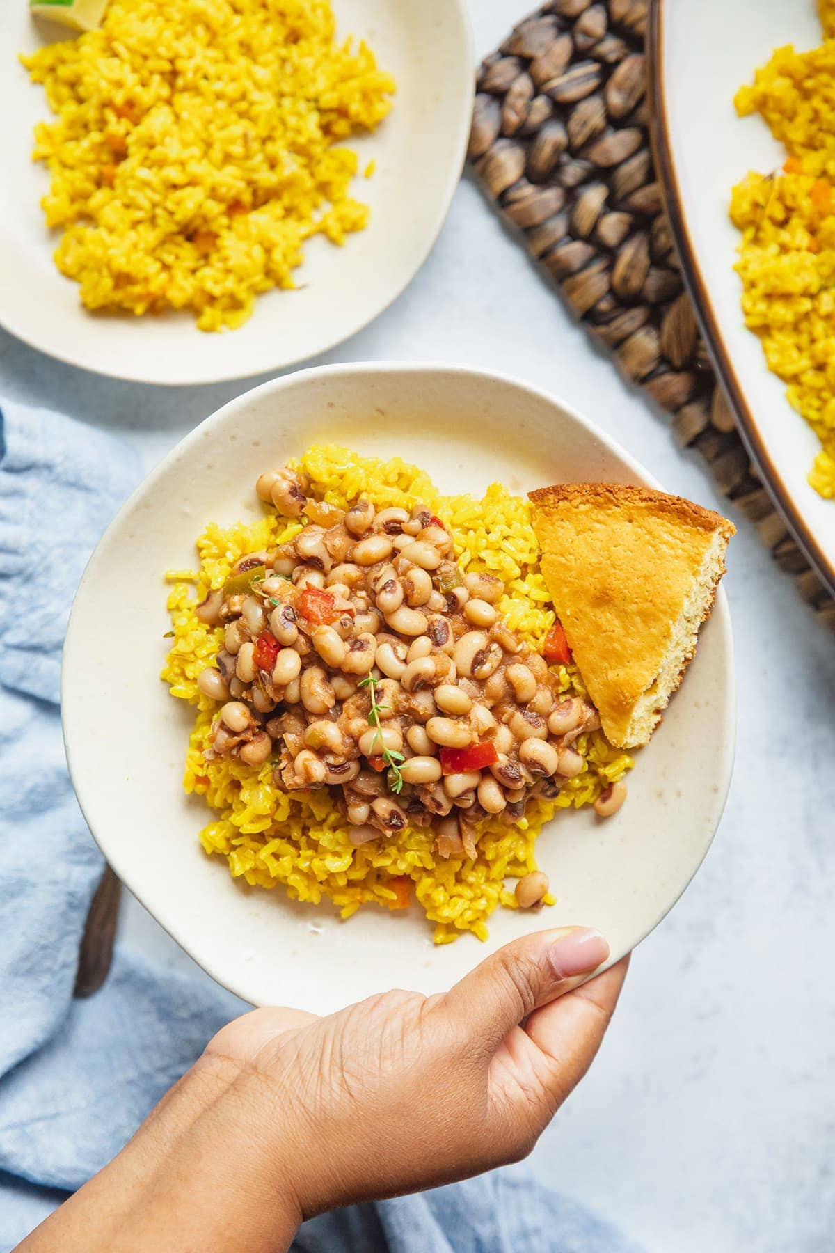 finished turmeric coconut rice on a white plate topped with vegan southern black-eyed peas on a white table