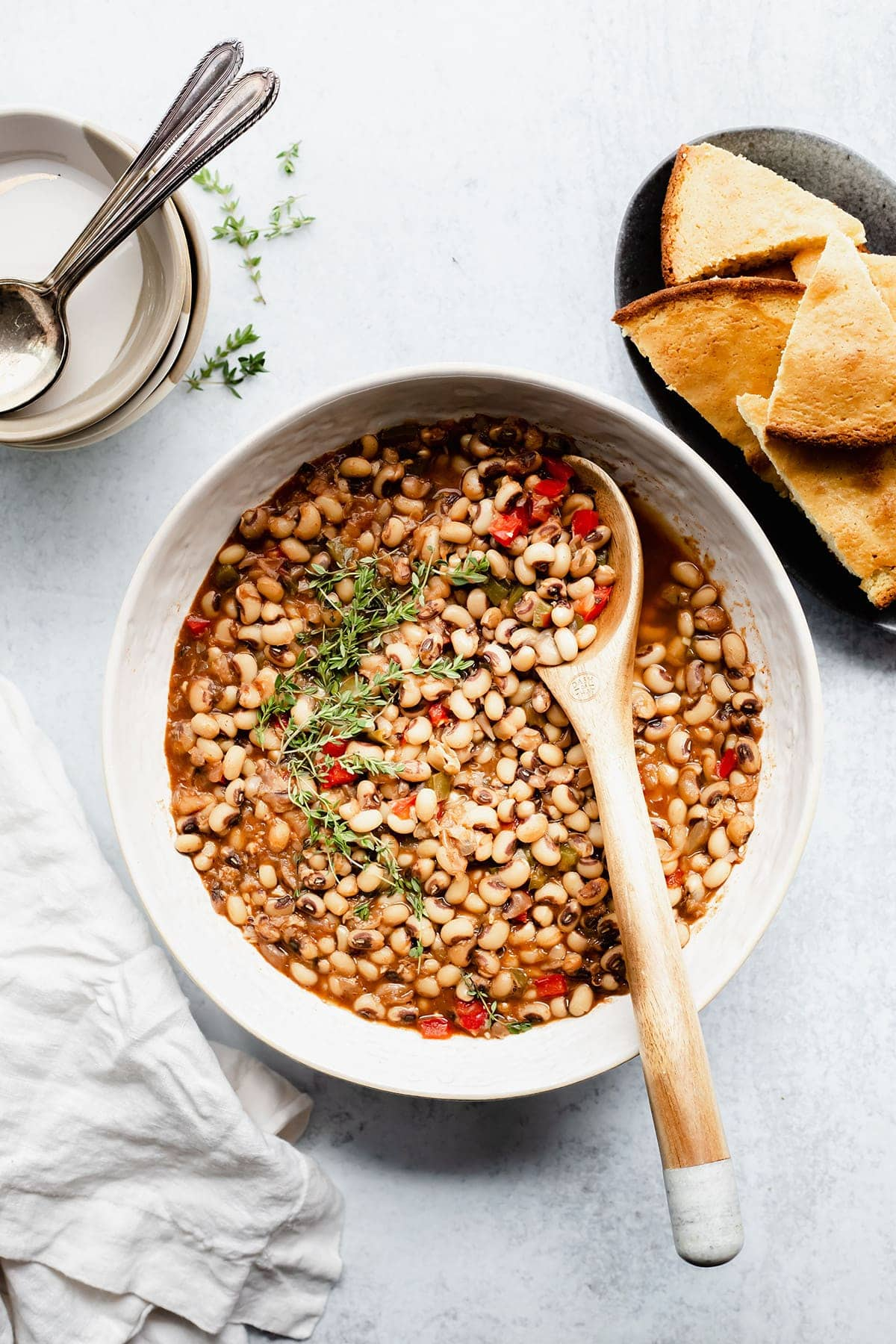 Overlay southern-style black-eyed peas with a wooden spoon, garnished with thyme in a white bowl with cornbread on a white background