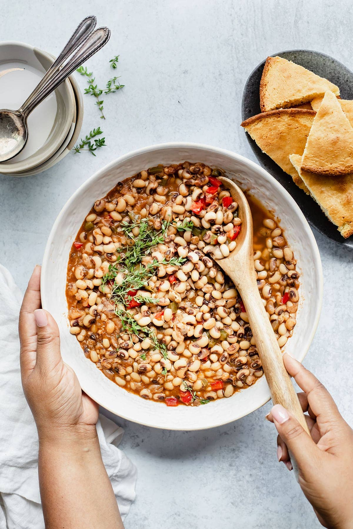 Bowl of vegan southern black-eyed peas being held with one hand and the other with a. spoon in the bowl on a white bowl on a white background