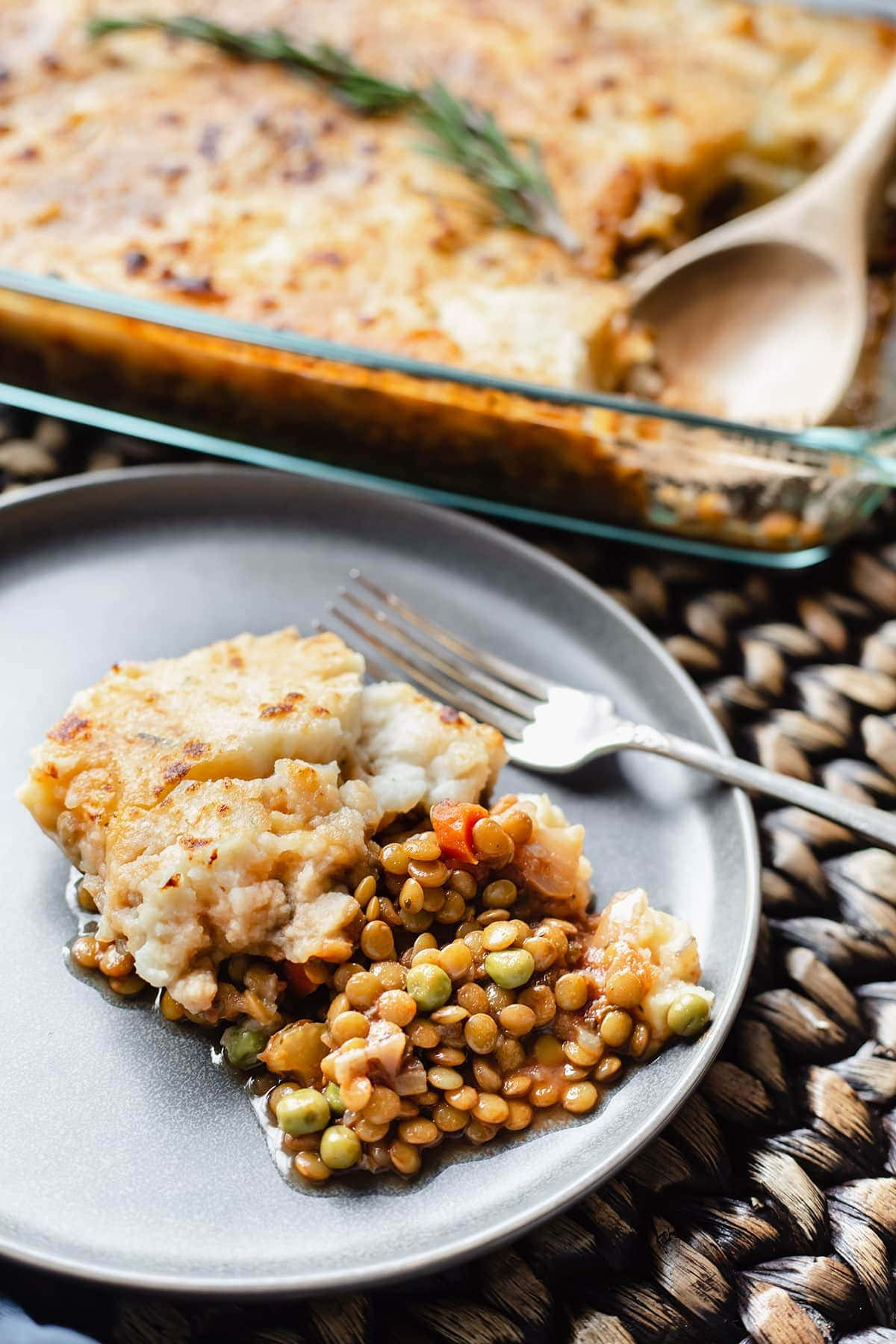 vegan lentil shepherd's pie overlay in a rectangular glass serving dish with a spoon with a serving in a grey plate on a brown background